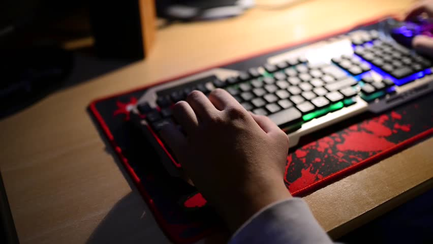 Teenage boy playing computer games, gamer mouse and keypad, focus on the boy hand, shallow depth of field. | Shutterstock HD Video #1019801893
