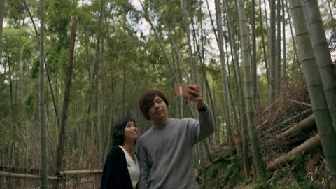 Young couple taking a picture together in a pathway in a bamboo forest in Kyoto, Japan with soft natural lighting.