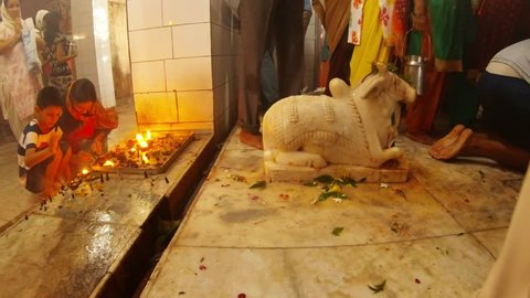 Rishikesh, Uttarakhand / India - July 30, 2018: Woman with little boy pray near candles legs of crowd around somebody pours water on statue of bull Nandi in hindu temple