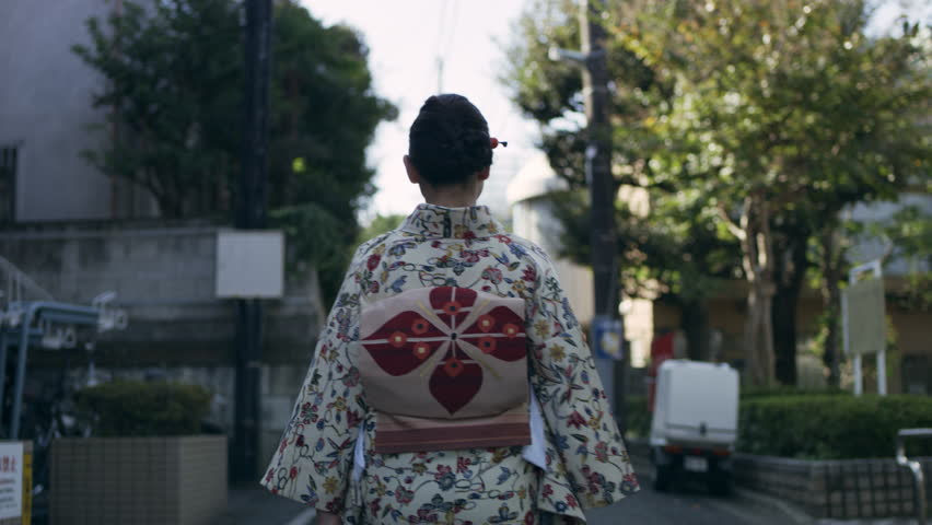 Back view of woman in kimono walking down a quiet residential street in a kimono in Japan, with soft day lighting. Medium shot on 4k RED camera.