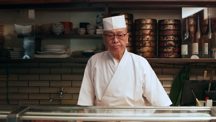 Portrait of veteran sushi chef with small smile standing behind a counter in his small traditional sushi bar with soft interior lighting. Medium shot on 4k RED camera. | Shutterstock HD Video #1019910583
