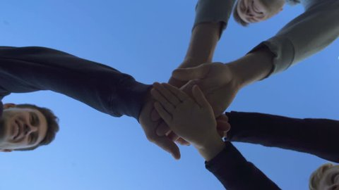 Group of friends put hands together, team work leads to victory, bottom view