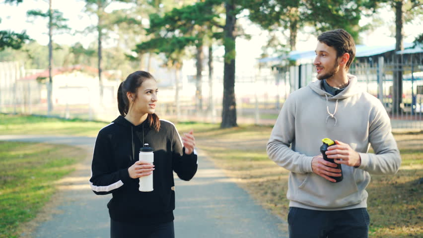 Young couple man and woman in sportswear are walking in forest holding water bottles, talking, laughing and drinking. Relationship, sports and leisure concept. | Shutterstock HD Video #1020069373