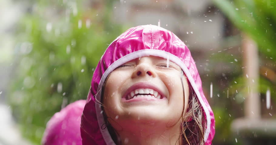 A happy girl is playing in the rain and is happy because she has fun. SHe opens his arms as a sign of freedom and love for nature. #1020073843