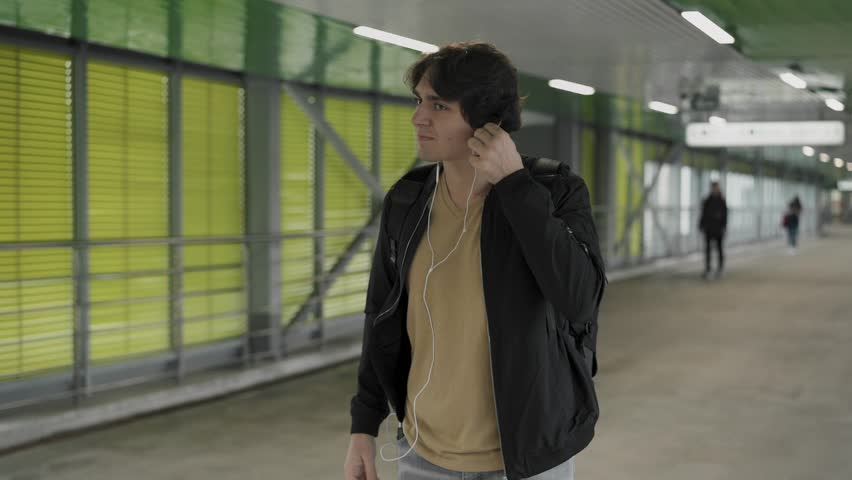 Handsome young man wearing black jacket putting on headphones, walking, dancing and singing along to his favourite song. Tracking slow motion medium shot | Shutterstock HD Video #1020108073