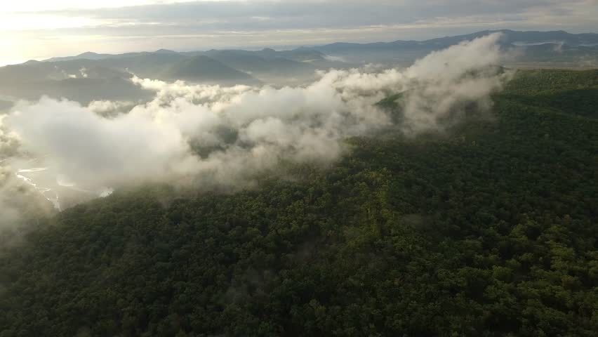 High altitude Drone forward beautiful mountain scenery through clouds steam smoke Early morning sun. Green forest trees cover slopes. Mystical view nature untouched wild. Brilliant meandering river. | Shutterstock HD Video #1020127423