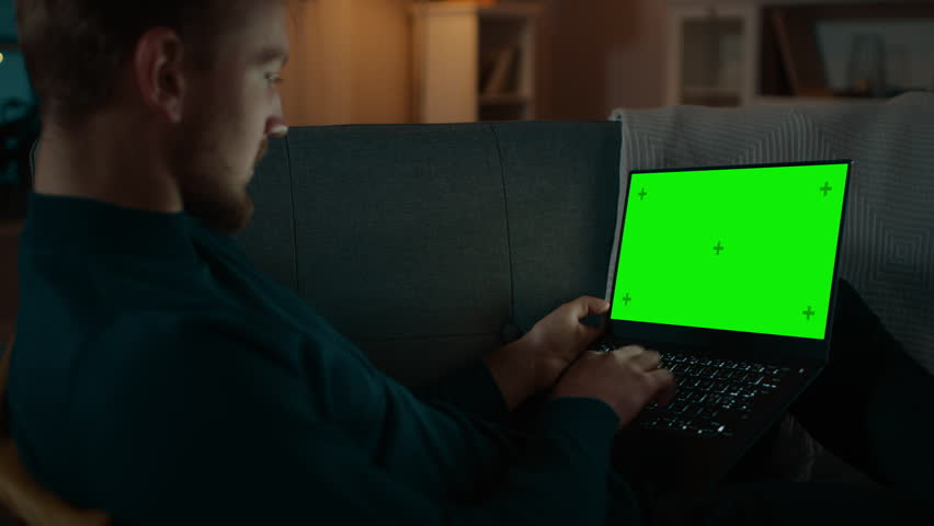 Man Sitting Relaxes on a Couch Works on a Laptop with Green Chroma Key Screen. Late at Night in His Living Room Man Uses Notebook Computer. | Shutterstock HD Video #1020144463