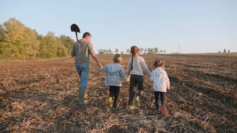 Farmer with his four children going on the farm field for work together. Farmer with his large family walking on the field, steadicam shot, rear view.