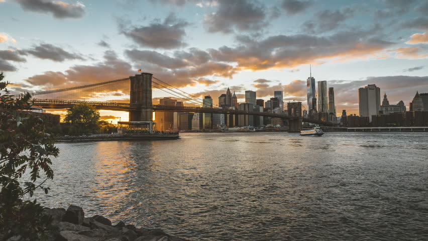 4k Timelapse movie film clip of New York City Manhattan, day to night transition with financial district skyline, cityscape at Brooklyn bridge park at day during sunset, with buildings, skyscrapers