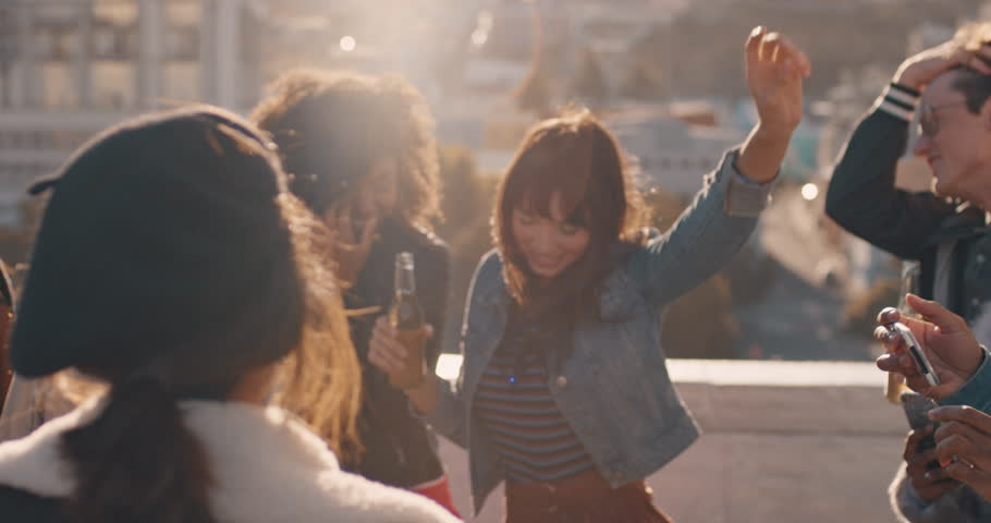 Slow motion group of multiracial friends hanging out young asian woman dancing enjoying rooftop party at sunset drinking alcohol having fun on weekend celebration | Shutterstock HD Video #1020198643