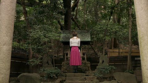Wide shot on 4k RED camera of somber Asian woman walking up to a shrine and bowing towards it in a beautiful garden with soft natural lighting.