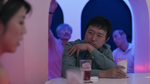 Pensive Japanese man drinking a cocktail and talking to a woman at the bar in a fun, cool bar with soft interior lighting. Medium shot on 4k RED camera on a gimbal.