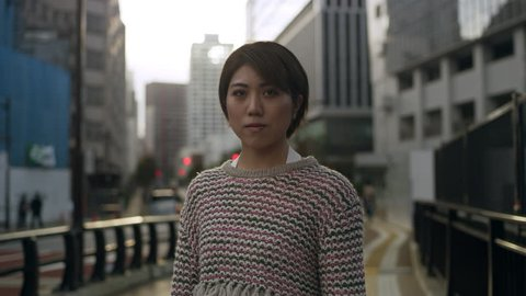 Portrait of Japanese woman standing in the middle of a quiet sidewalk in a metropolitan city in Japan with soft natural lighting. Medium shot on 4k RED camera.