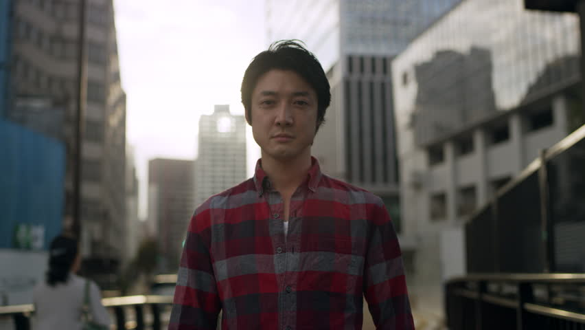 Portrait of Japanese man standing in the middle of a sidewalk in a metropolitan city in Japan with soft natural lighting. Medium shot on 4k RED camera.