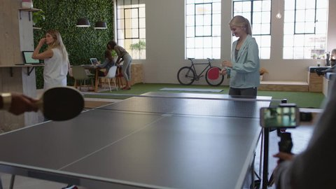young business people playing ping pong in office enjoying competitive fun colleague using smartphone sharing game on social media