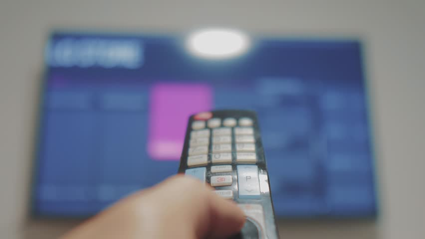 Smart tv with apps and hand. Male hand holding the remote control turn off smart tv. man hand controls TV holding remote. concept internet lifestyle online cinema | Shutterstock HD Video #1020338503