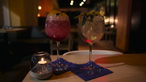 Two craft cocktail drink in a upscale cocktail lounge and a woman's hand picking up one of them.
