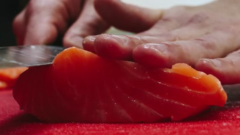 Chef takes out bones from the salmon fillet, cutting fish on slices for cooking sushi in 4k resolution in slow motion