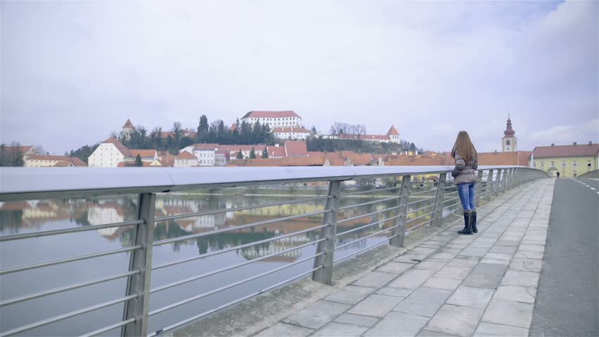 Woman walking on bridge with Ptuj city in background HD. Young attractive female person in jacket walking beside iron fence on bridge, enjoying view of old city and big river.