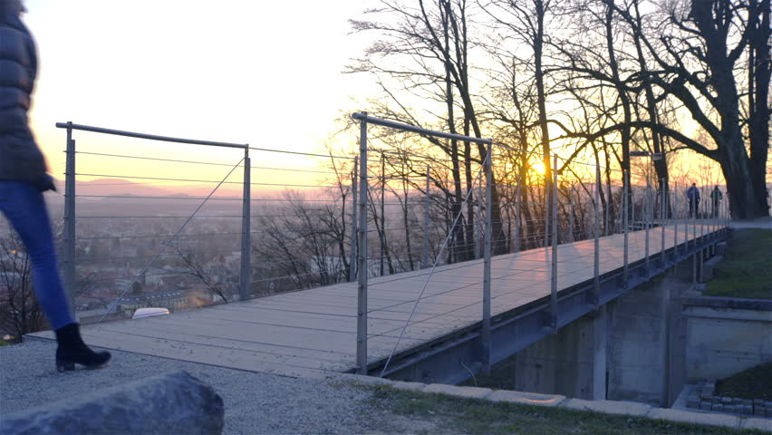Person walk over bridge with sunset in background HD. Woman alone walking over pedestrian iron bridge while sun going down far in background behind the trees.