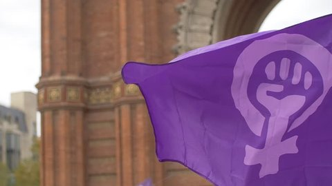 Feminist Flag waving in front of Arc de Triomf in Barcelona. Feminist Activists in a Demonstration. March for the International Day of Nonviolence against Women and Children in Barcelona, Spain.