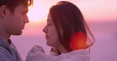 Unhappy couple embracing woman being comforted by partner is sad on beach at sunset slow motion RED DRAGON