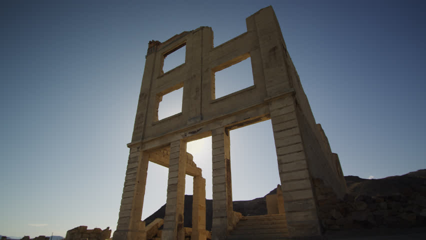 The Setting Desert Sun Peeks through the Doorway of the Famous Cook Bank Ruins in Rhyolite, Nevada. (Sun Event begins at :05 sec) | Shutterstock HD Video #1020436393