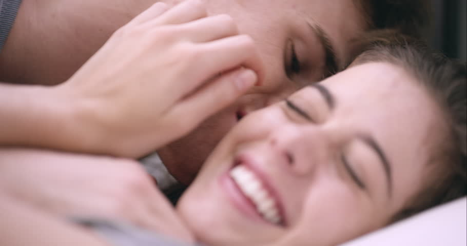 Close up of Attractive young couple kissing engaged in foreplay touching each other