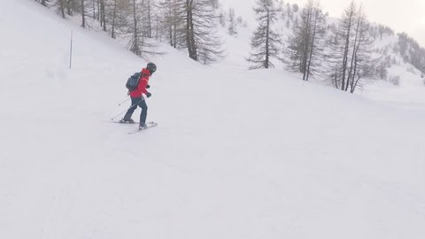 Man skiing on snow in the mountains, slow motion. Young man going downhill with ski and having fun on the slope in the Alps, Italy. Winter sport and activities.