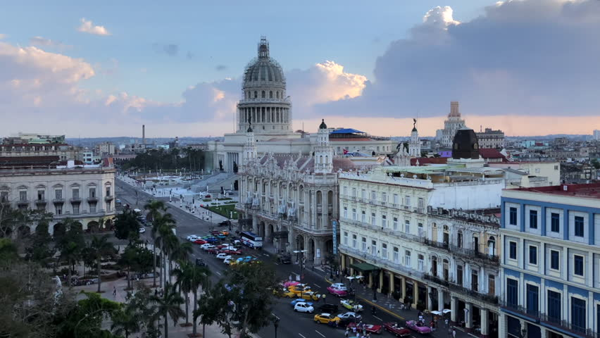 Time Lapse of lively Havana street near main sightseeings;old spanish colonial facades, vintage architecture of Grand Theater on Paseo del Prado; lots of tourists and retro cars; cuban summer sunset