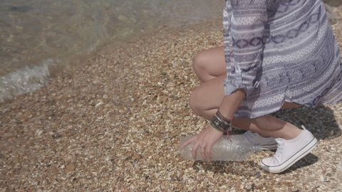 Close Up Shot Of Young Woman Reaching Down To Pick Up Plastic Bottle On Beach In Slowmotion - Ungraded