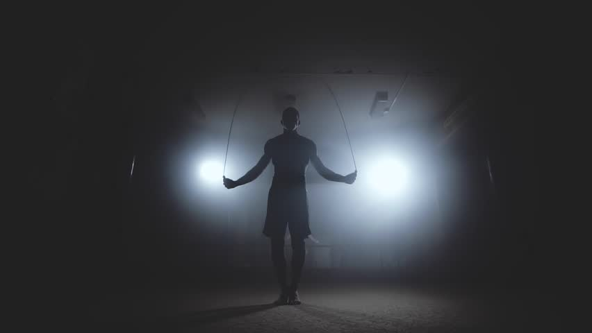 Fighter does some jump rope exercises in dark room under light. Boxer training in smoky studio in slow motion. Silhouette on dark background. Medium shot | Shutterstock HD Video #1020490693