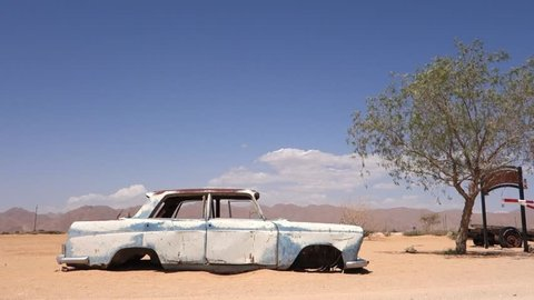 Solitaire, Namibia - 12 19 2017: Solitaire, December 19, 2018: Cinematic old and rusty car wreck at the last gas station before the Namib desert. Solitaire, Namibia.