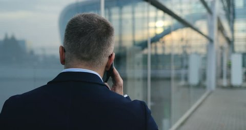 Back view on the Caucasian businessman in glasses walking the street at the office center and talking on the phone. Close up. Rear. Outside.
