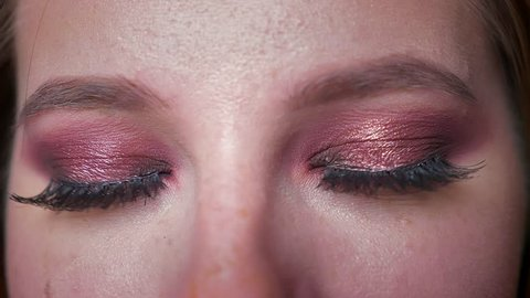 Amazing glance, eyes of caucasian woman close up in pink glowing eyeshadows looking at camera calmly with concentration, indoors