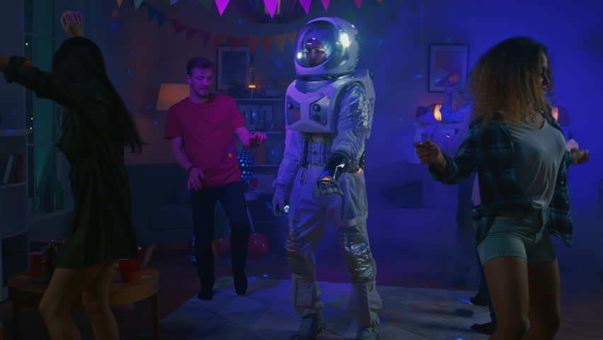 At the College House Costume Party: Fun Guy Wearing Space Suit Dances Off, Doing Groovy Funky Robot Dance Modern Moves. With Him Beautiful Girls and Boys Dancing in Neon Lights. In Slow Motion. | Shutterstock HD Video #1020544123