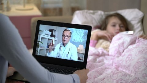 Medicine online. Mom with a little sick daughter gets a doctor's advice using video chat at home. Male doctor prescribing her a nosal medicine for a cold.