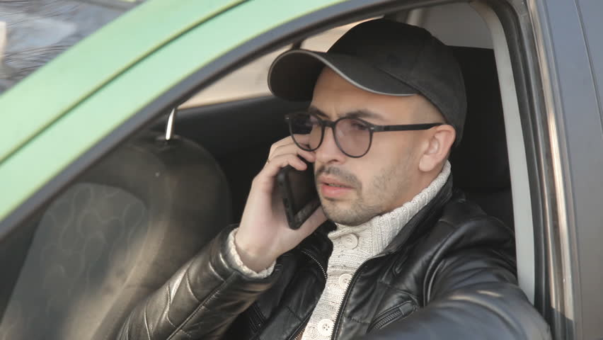 A private detective or a spy conducts surveillance of the object of surveillance. A man secretly taking pictures from the car window | Shutterstock HD Video #1020566713