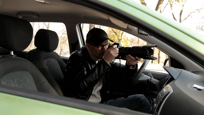 A private detective or a spy conducts surveillance of the object of surveillance. A man secretly taking pictures from the car window | Shutterstock HD Video #1020566743