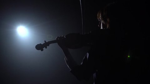 Musician plays the violin while standing with his back glare from a lantern. Black smoke background. Back view