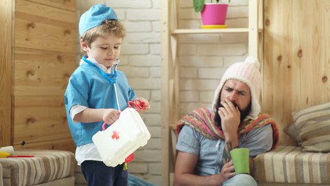 Boy and father play physician and patient. The boy in the doctor's suit treats a bearded man in a knitted hat. Concept of a medical case