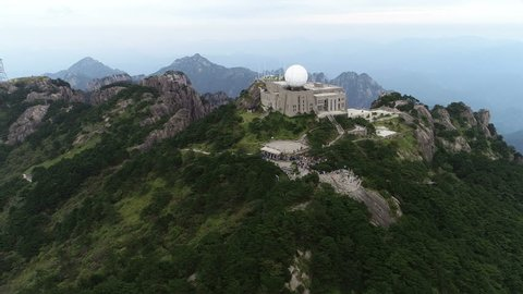 HUANGSHAN, CHINA - SEPTEMBER 2018: Aerial drone shot of meteorological weather station and viewing platform on mountain peak in Huangshan national park in China