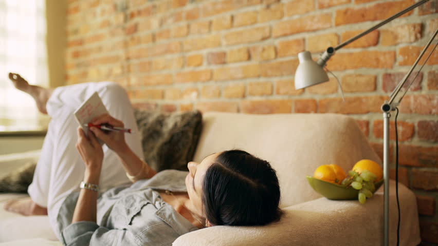 Woman lying on the sofa and doing notes in notebook