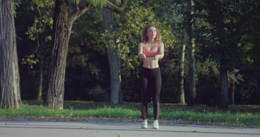 Young Athlete Woman in Comfortable Sport Outfit Jumping Rope on a Sports Field in the Park. | Shutterstock HD Video #1020635293