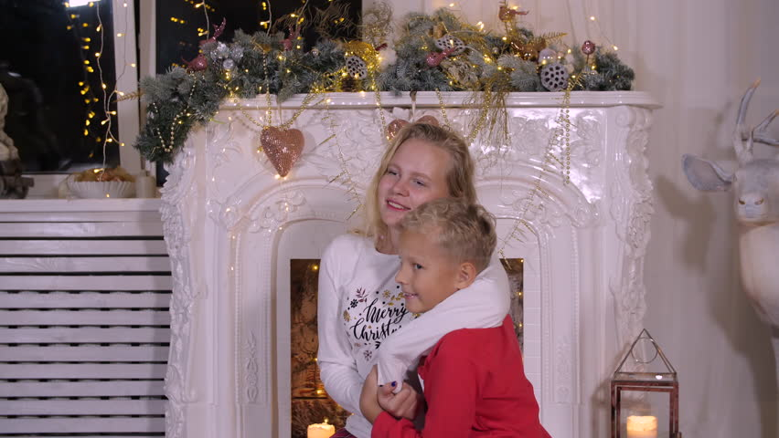 Smiling sister hugging little brother in red pullover on Christmas fireplace background. Happy sister and brother waiting New Year night front decorative fireplace. Family holiday, Christmas concept | Shutterstock HD Video #1020640783