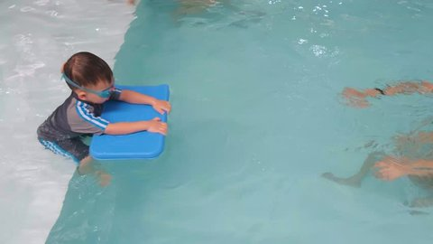 Cute little Asian 2 years old toddler boy child kicking feet in swimming costume wear swimming goggles use floating board learn to swim at indoor pool,  Swimming school for small children, slow motion