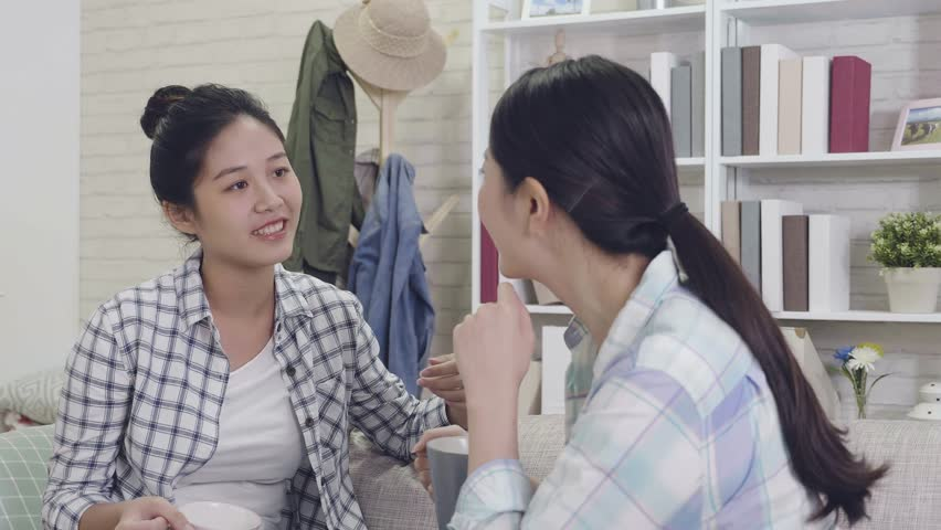 Slow motion roommates talking sitting on a sofa in living room in a house interior. young asian girls chatting with a surprised face while listen to news. friends relaxing on couch lifestyle concept. | Shutterstock HD Video #1020683203