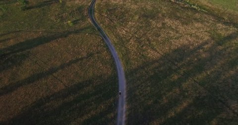 Aerial MTB.MTB Bike Cycling Riding From Drone.Senior Man Riding Mountain Bike.Aerial Man Cycling Along Country Road. Man On MTB Bicycle Aerial Drone View. Cycling In Sunset From Drone.Cyclist Drone.