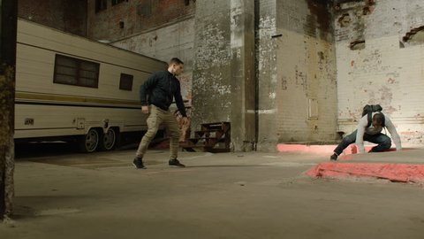 Wide shot of Angry man thrown to the ground by a stronger man in front of an abandoned camper trailer in an old warehouse in moody lighting. Medium shot in 4K with an Alexa Mini camera
