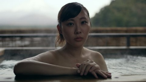 Portrait of a thoughtful Japanese woman sitting in a hot water bath in a traditional spa with view of Mount Fuji in the background with soft natural lighting. Close up shot on 4k RED camera.
